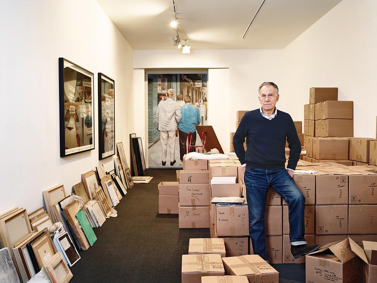 Yvon Lambert, leggendario gallerista francese, in posa per il fotografo l'ultimo giorno di apertura dello spazio. Allineate lungo la parete le opere di piccolo formato.